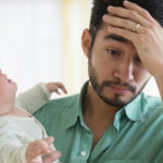 Frustrated father holding crying baby
